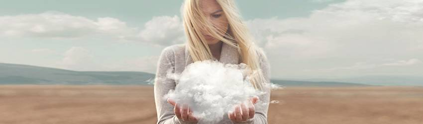 A blonde woman is standing in a field holding a cloud in her hands.