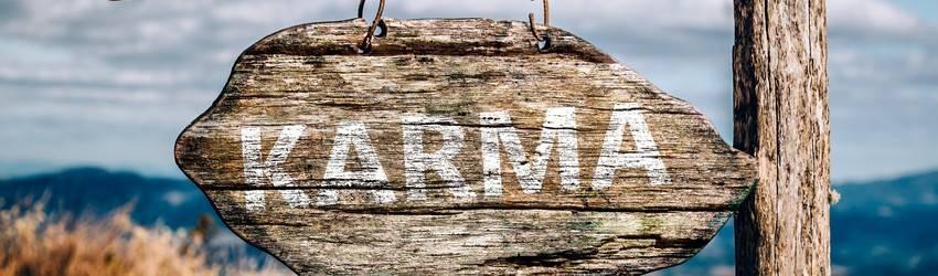 A sign on a beach says KARMA on it.