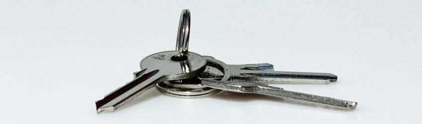 Silver metal keys on a white table.
