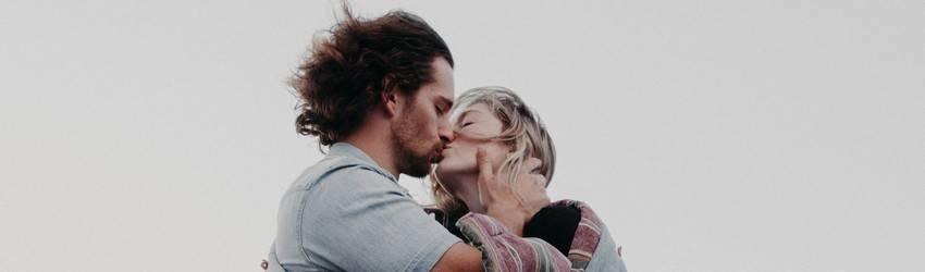 A couple kisses on a clifftop against a grey sky.
