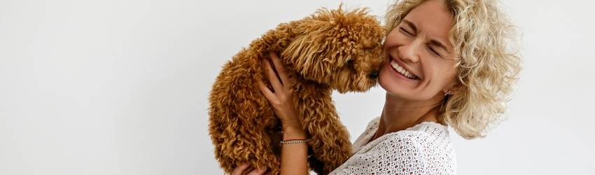 A woman holds a brown dog up to her face.