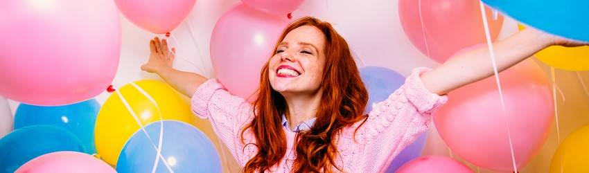 redheaded woman surronded by balloons smiling