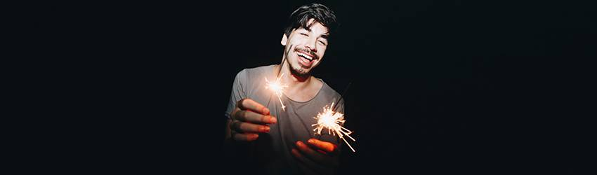 A Leo man stands holding two sparklers and laughing.
