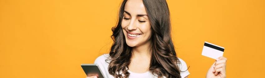 woman smiling holding her credit card while viewing something on her phone