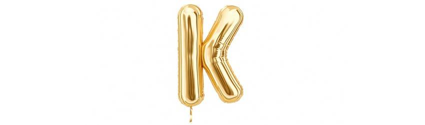 A gold foil balloon in the shape of a K floats on a white background.