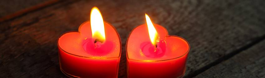 Two red heart candles representing twin flames.