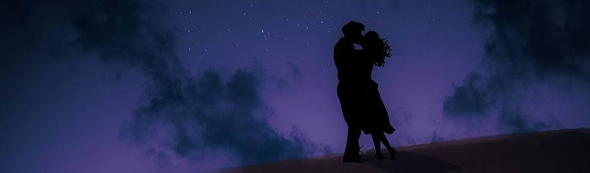 Two lovers kiss on the top of a hill under a new moon.