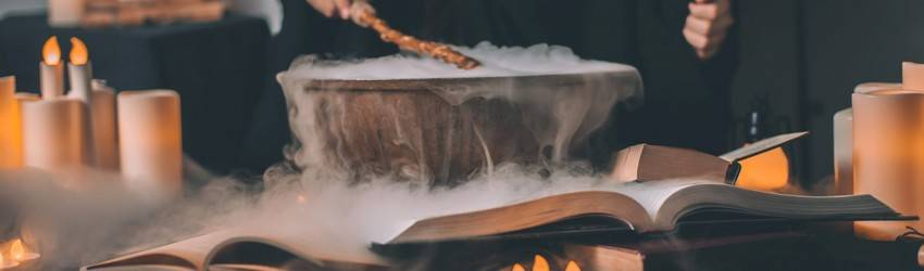A person is making a magic spell over a cauldron with smoke around it.
