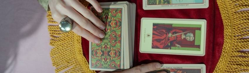 Two hands on top of a tarot deck pick tarot cards.