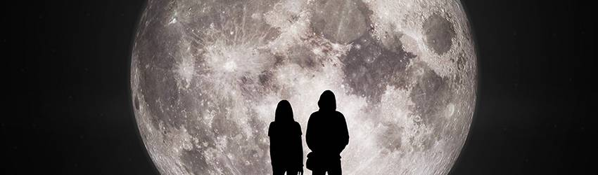 Two people hold hands in front of a large full moon.