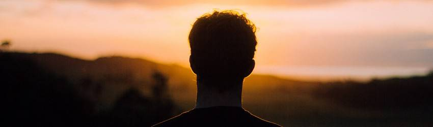 A silhouette of a man stands in front of an orange sunset.
