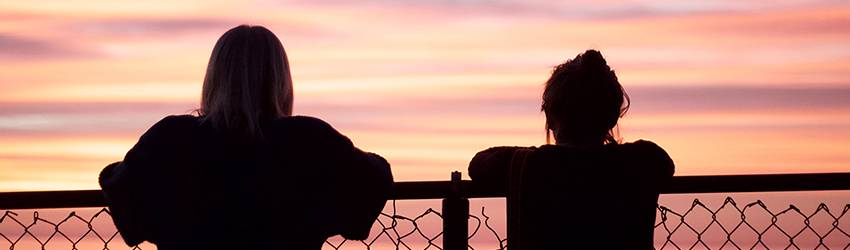 Two shadowy people lean against a chain-link fence and watch the pink and orange sunset over the ocean.