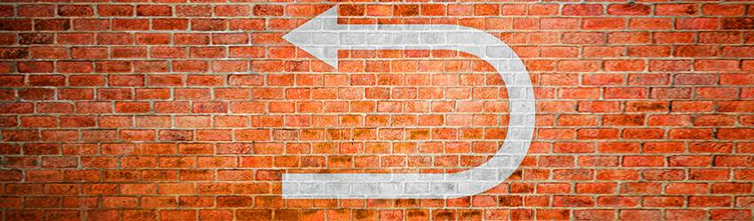 A reverse arrow on a red brick wall indicating a retrograde on the red planet, Mars.