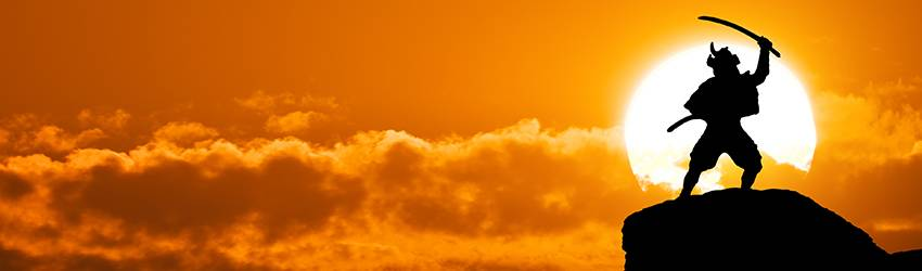 A samari stands at the top of a hill in front of a blazing sun.