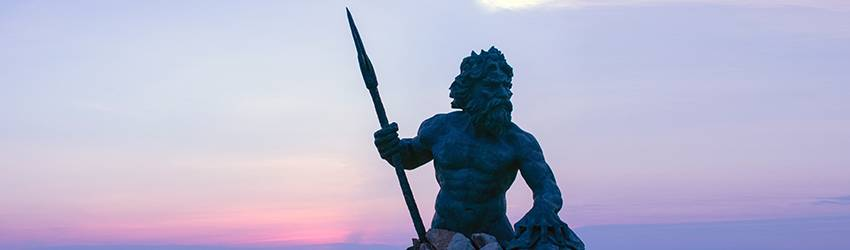 A statue of king Neptune in front of a sunset.
