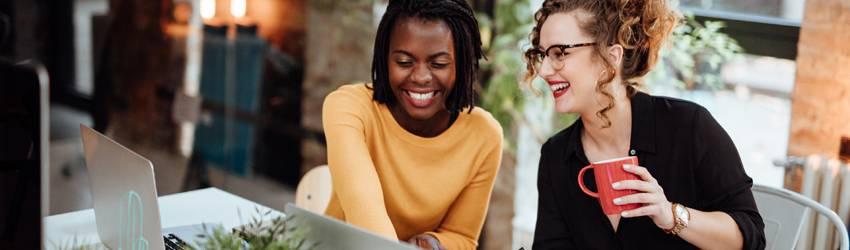 Two women sit at work brainstorming.