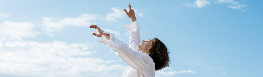 A figure wearing a white shirt dances against the baby blue sky with fluffy white clouds.