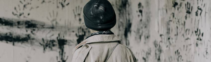 A person starring at paint handprints all over a wall in the color black. Representing a struggle and out-of-body experience.