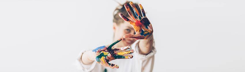 A woman wearing all white holds her hands up to the camera - they are covered in multicolored paint.