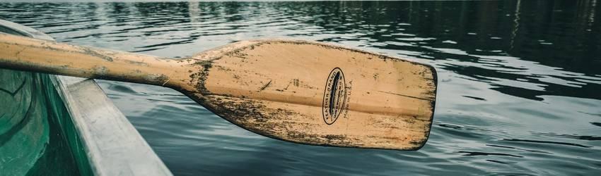 An oar on the side of boat above water in a dream.