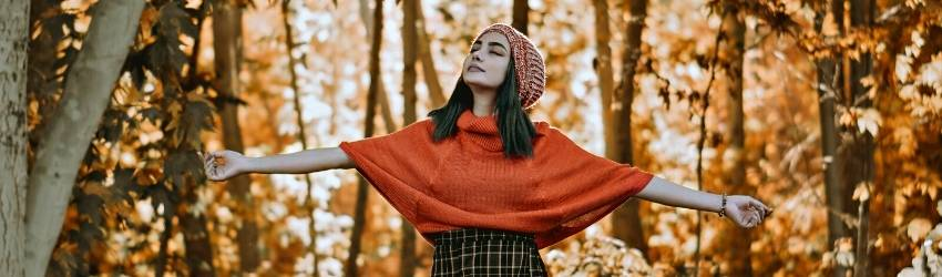 A young woman with brown hair wearing an orange poncho, plaid skirt, and marled red cap holds her arms out, closing her eyes, and looking up towards the sky. She is standing in a forest whose trees are turning golden with the fall season.