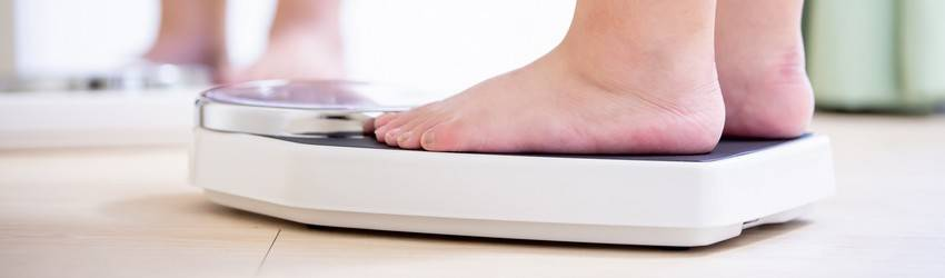 A person steps on a scale representing a weight change.