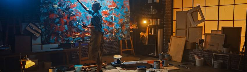 A person painting an abstract piece in a dark studio surrounded by paint cans.