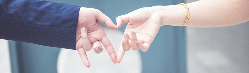 Two people make a heart with their hands.