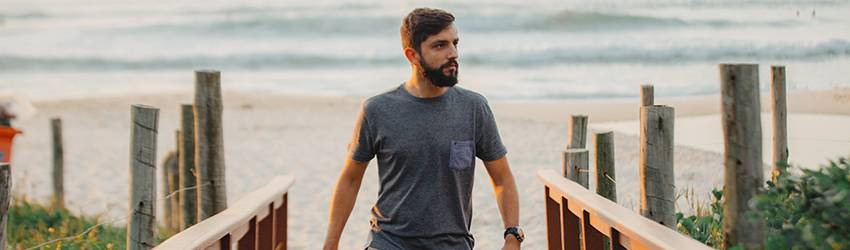 A man walks away from the beach with a camera in hand. He is brunette with a scruffy beard, wearing a blue t-shirt and tan khakis.