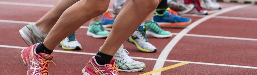 A bunch of people are at the starting line of a running race. Their feet have just left the starting blocks.