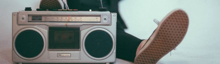 A person sits behind a large boombox radio.