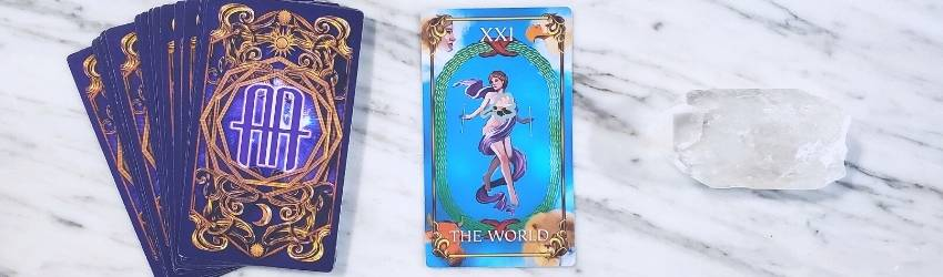 the world tarot card on a table with a crystal and other tarot cards