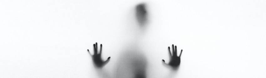 A person presses their hands on a pane of glass from the beyond.