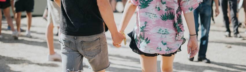 Two people walking in a crowd of people near the boardwalk holding hands.
