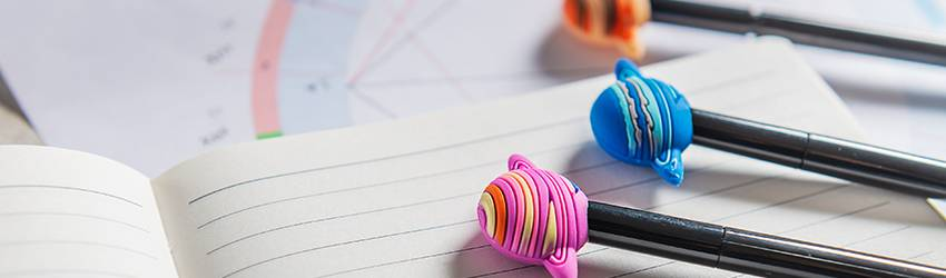 Three pencils lay on a notebook. They have planet erasers at the end of them.