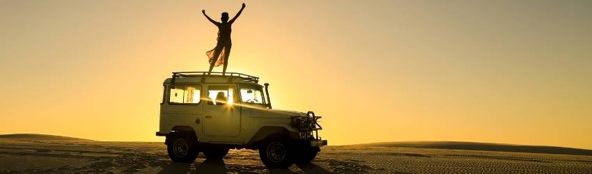 A woman stands on top of a jeep, the sun creates a beautiful shadow around her as she embraces the sun energy.