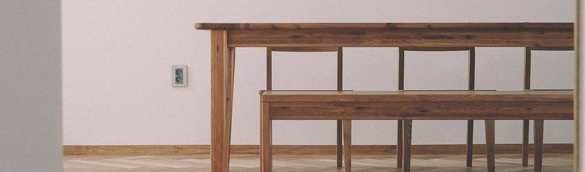 A table sits in an empty room with nothing on it.