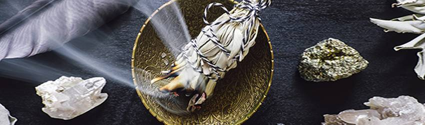 Sage burning in a golden bowl surrounded by crystals.