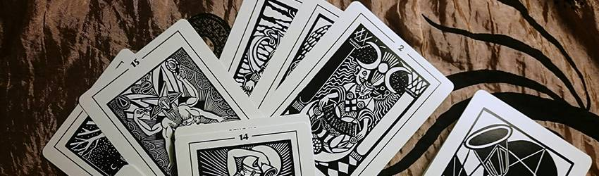 A pile of black and white tarot cards on a wooden table.