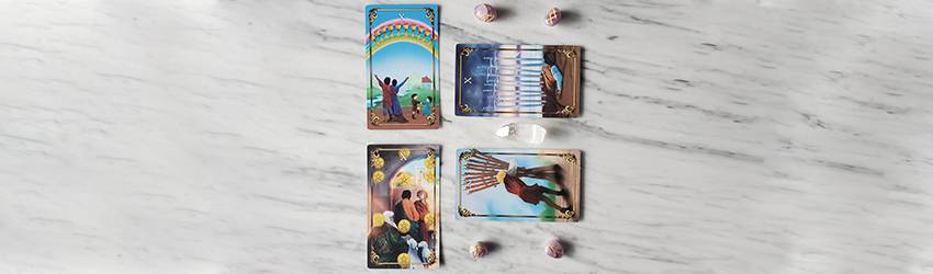 The 10s of the Tarot Minor Arcana sit on a marble table surrounded by crystals.