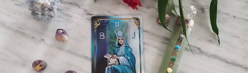 The Empress card sits on a marble table with crystals.