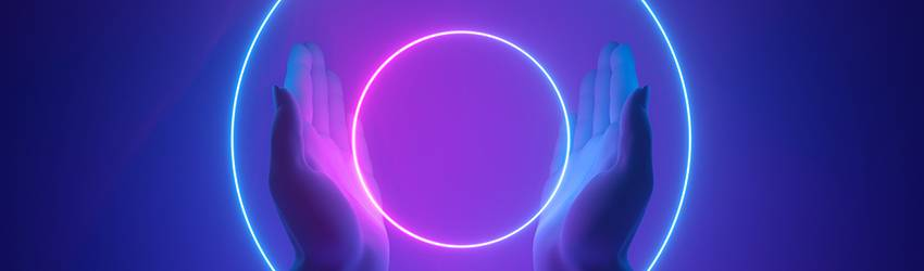 A person holds two rings of neon purple lights between their hands.