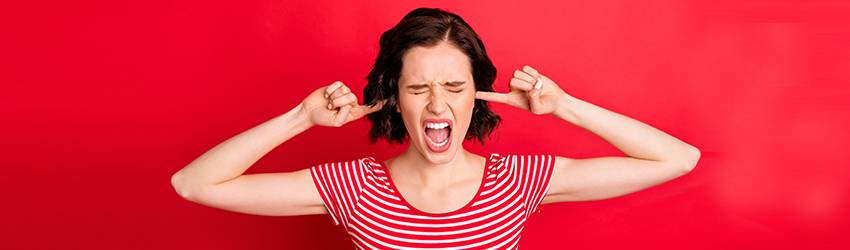 A woman wearing red on a red background closes her eyes and plugs her ears in anger. She seems to be yelling.