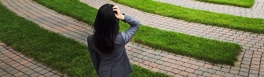 A person in a business suit holds their head while looking at a grass maze.