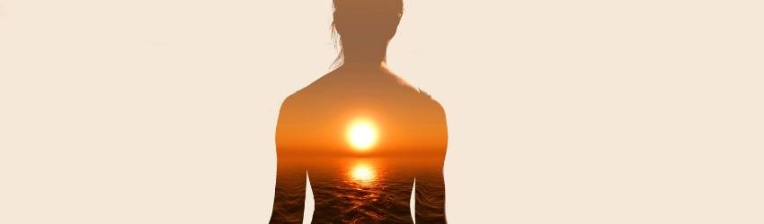 A woman meditates as a sunrise is overlaid through her body. This represents that chakra energy that is being ignored.