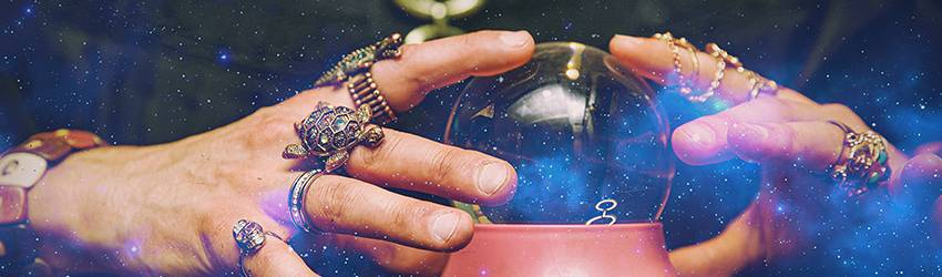 An astrologer holds their hands around a cliche crystal ball.
