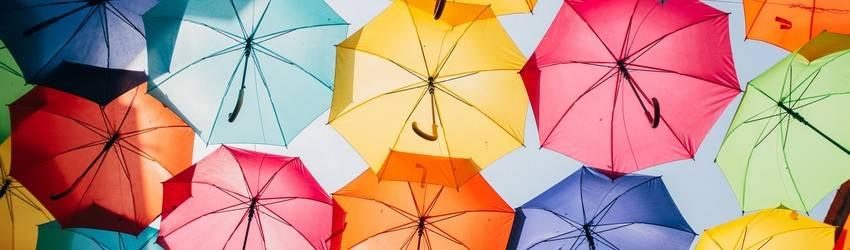 There are 20 colorful umbrellas covering the sky. The photo is taken from underneath them.