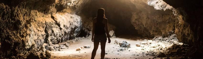 A person walks through an underground cave system.