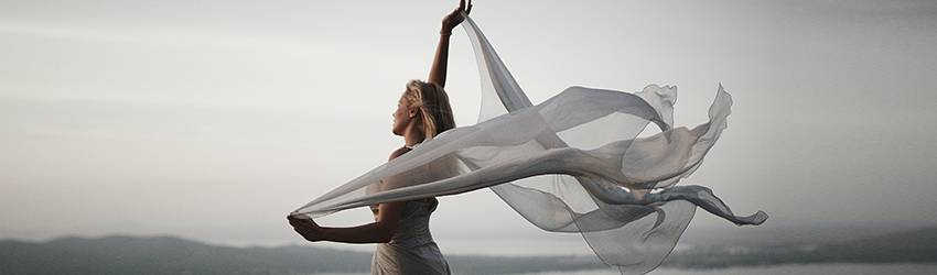 Woman standing in the wind on a cliff with a long white scarf flowing out behind her.