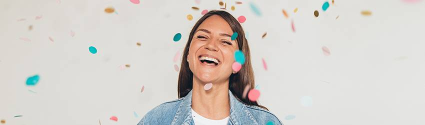 A woman stands smiling under colorful confetti.